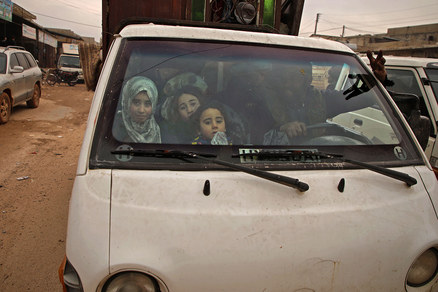 Displaced Syrians in a truck transporting their belongings pass through the town of Hazano in the northern countryside of Idlib, on Feb. 4, fleeing north amid an ongoing regime offensive. AAREF WATAD/AFP via Getty Images