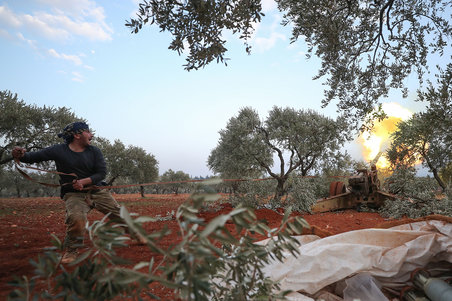 A rebel fighter fires a cannon amid clashes with government forces in the last major rebel bastion of Idlib in northwestern Syria on Feb. 6. OMAR HAJ KADOUR/AFP via Getty Images