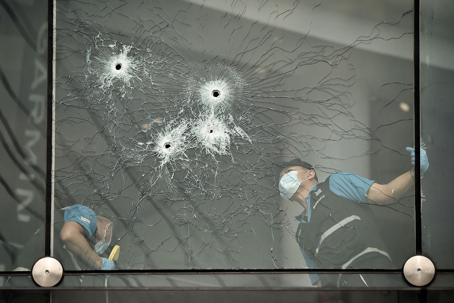 Forensics police inspect bullet holes inside the Terminal 21 shopping mall where a mass shooting took place in the Thai northeastern city of Nakhon Ratchasima on Feb. 10. A Thai soldier killed 29 people and holed up in a mall overnight before being shot dead by commandos. LILLIAN SUWANRUMPHA/AFP via Getty Images
