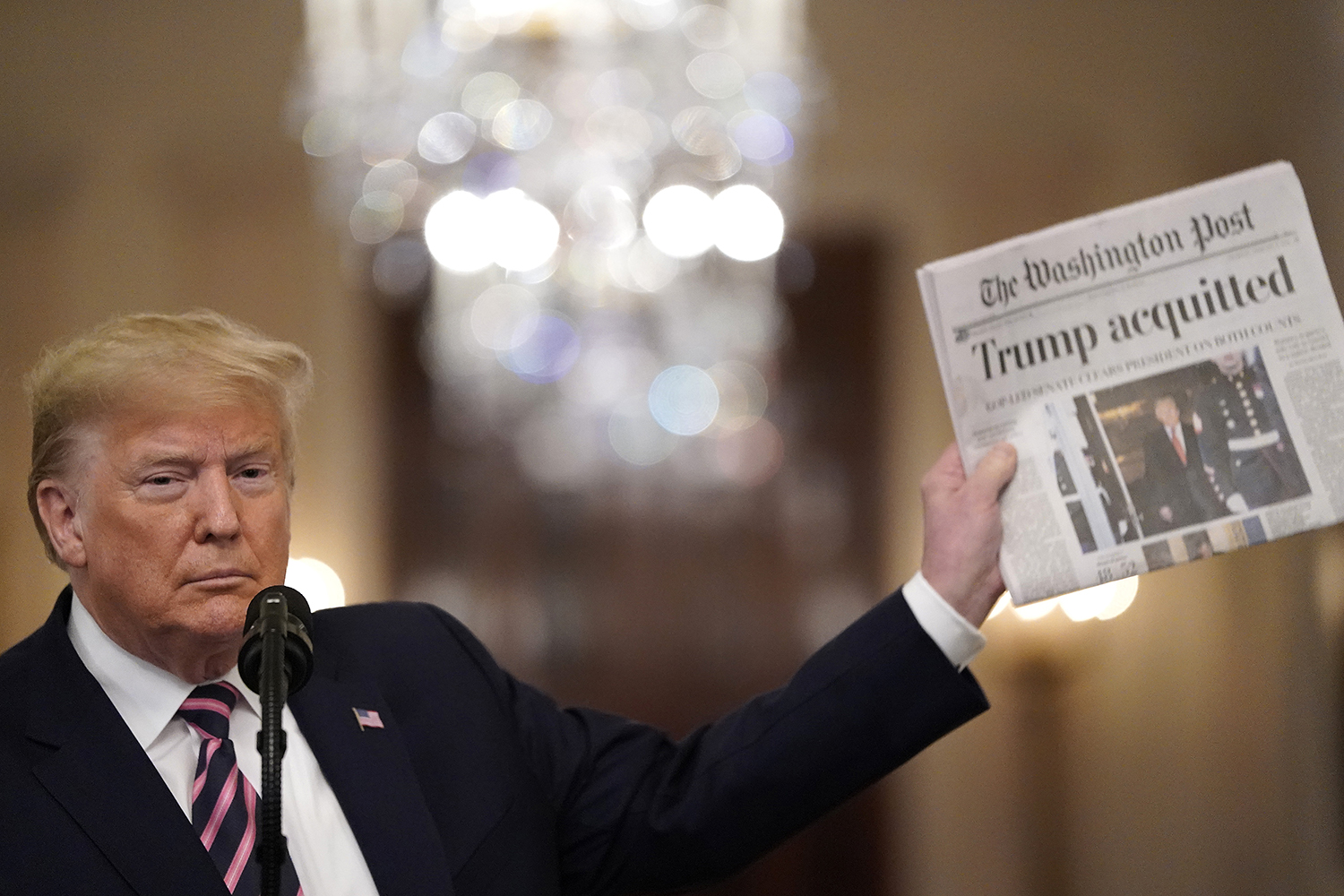 Trump holds a copy of the Washington Post as he speaks in the East Room of the White House on Feb. 6, one day after the U.S. Senate acquitted him on two articles of impeachment. Drew Angerer/Getty Images