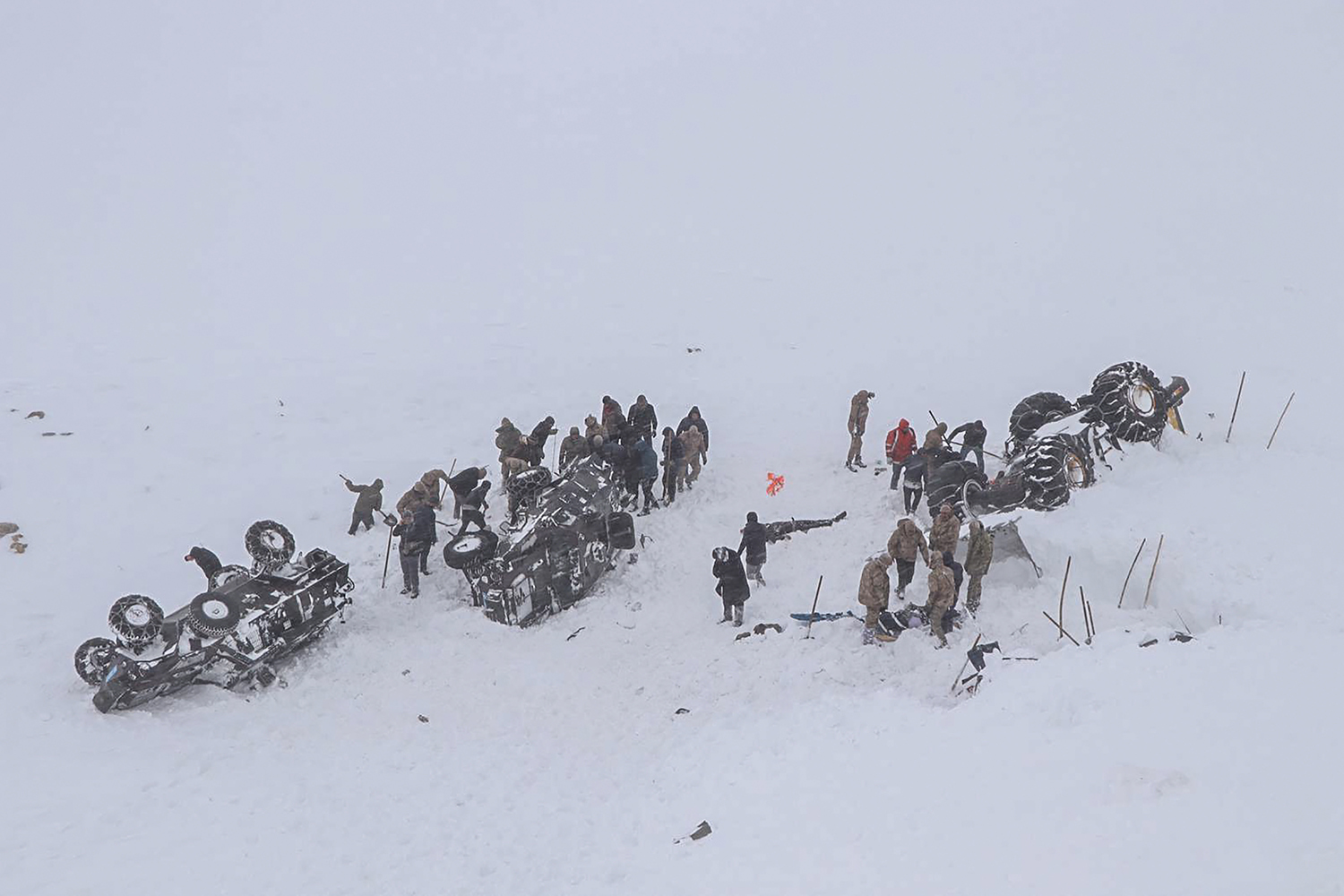 Emergency service members dig in the snow near the town of Bahcesehir, in eastern Turkey, on Feb. 5, as they search for dozens of rescue workers missing after being hit by a second avalanche while on a mission to find two people who vanished in a previous snow-slide. -/DHA/AFP via Getty Images