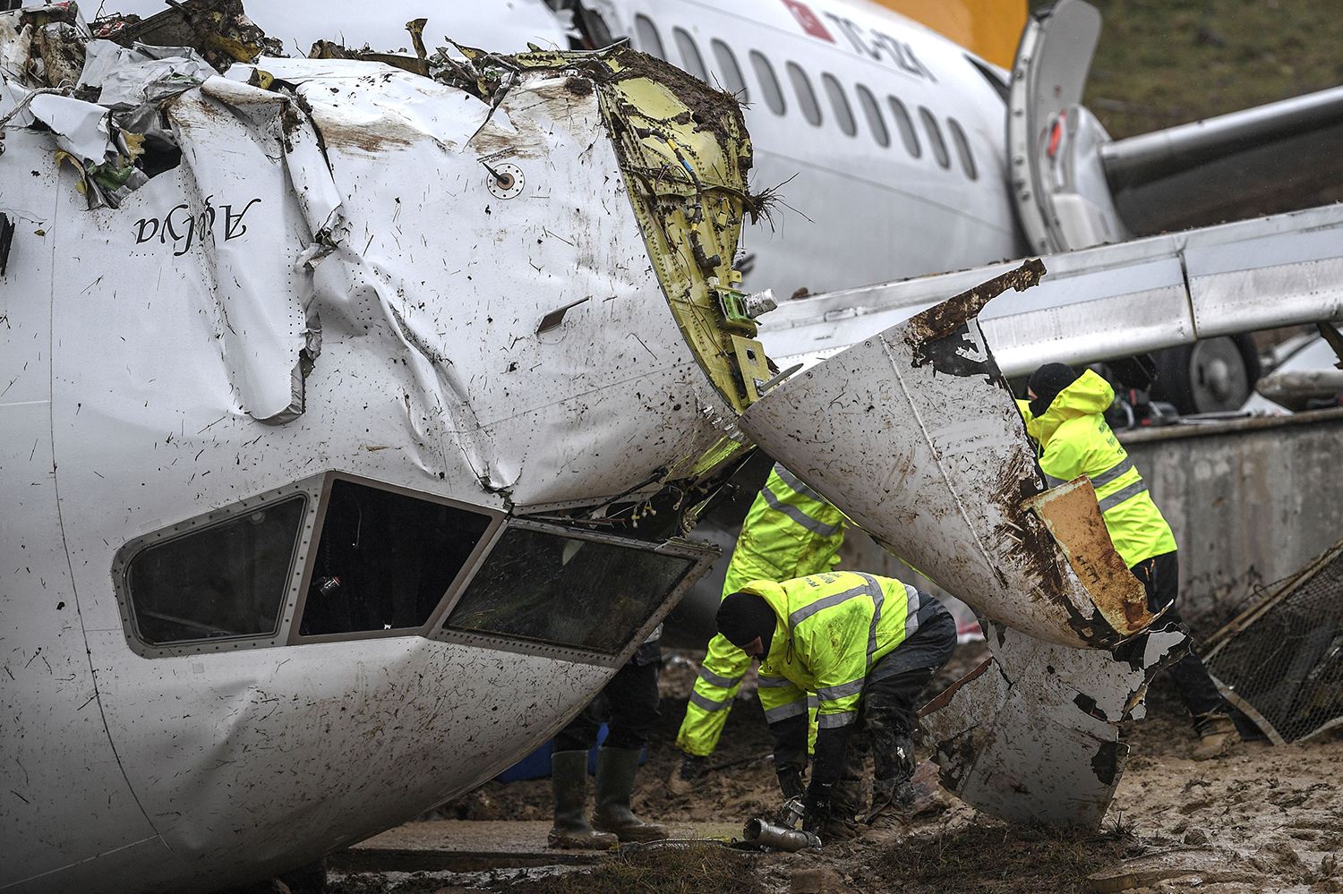 Turkish Pegasus airline members inspect the wreckage of the Pegasus Airlines Boeing 737 airplane that skidded off the runway upon landing at the Sabiha Gokcen airport, in Istanbul, on Feb. 6. Three people died and 179 were injured when the plane caught fire and split into three after landing in rough weather. OZAN KOSE/AFP via Getty Images