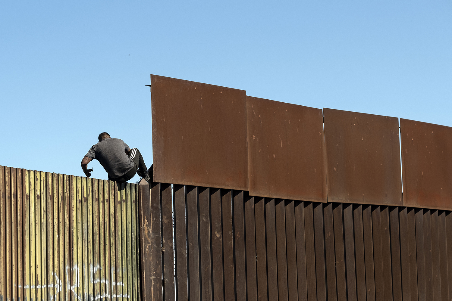 A man crosses over the U.S.-Mexico border fence from Mexicali to Calexico on Feb. 11. GUILLERMO ARIAS/AFP via Getty Images