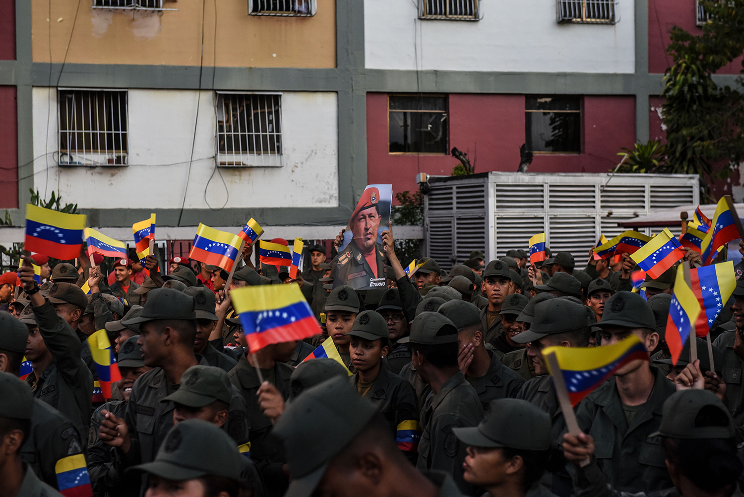 Venezuelan army soldiers raise the national flag while taking part in a rally in Caracas on Feb. 4 to commemorate the coup led by late president Hugo Chavez 28 years ago. YURI CORTEZ/AFP via Getty Images