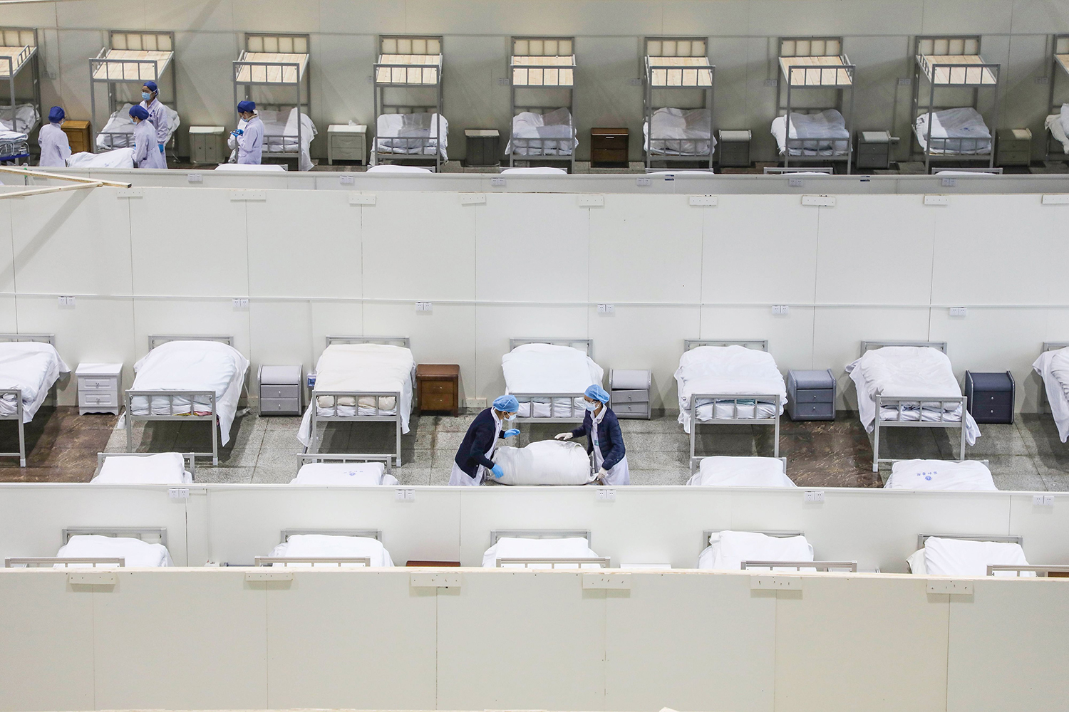 Medical staff members and workers set up beds as they prepare to accept patients displaying mild symptoms of novel coronavirus infection at an exhibition center converted into a hospital in Wuhan, China, on Feb. 5. STR/AFP via Getty Images