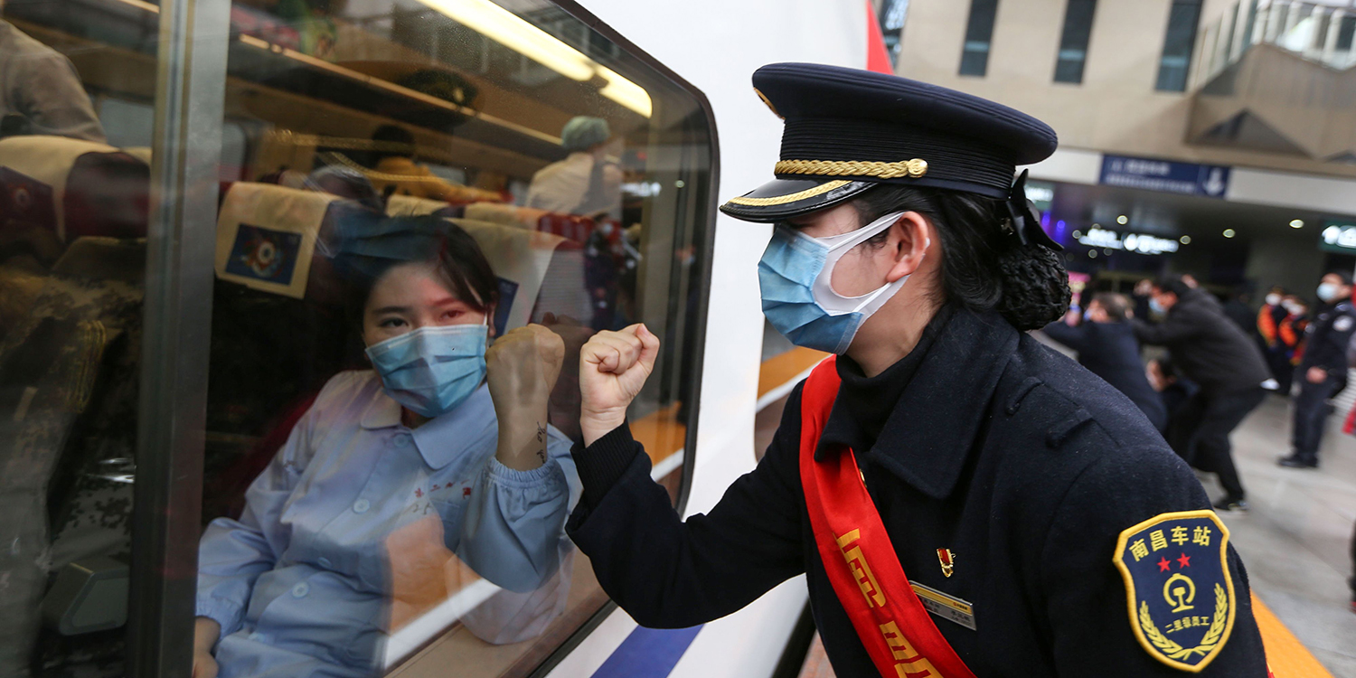 A train attendant gestures support to medical staff as they leave for Wuhan in Nanchang, in China's Jiangxi province, on Feb. 13.