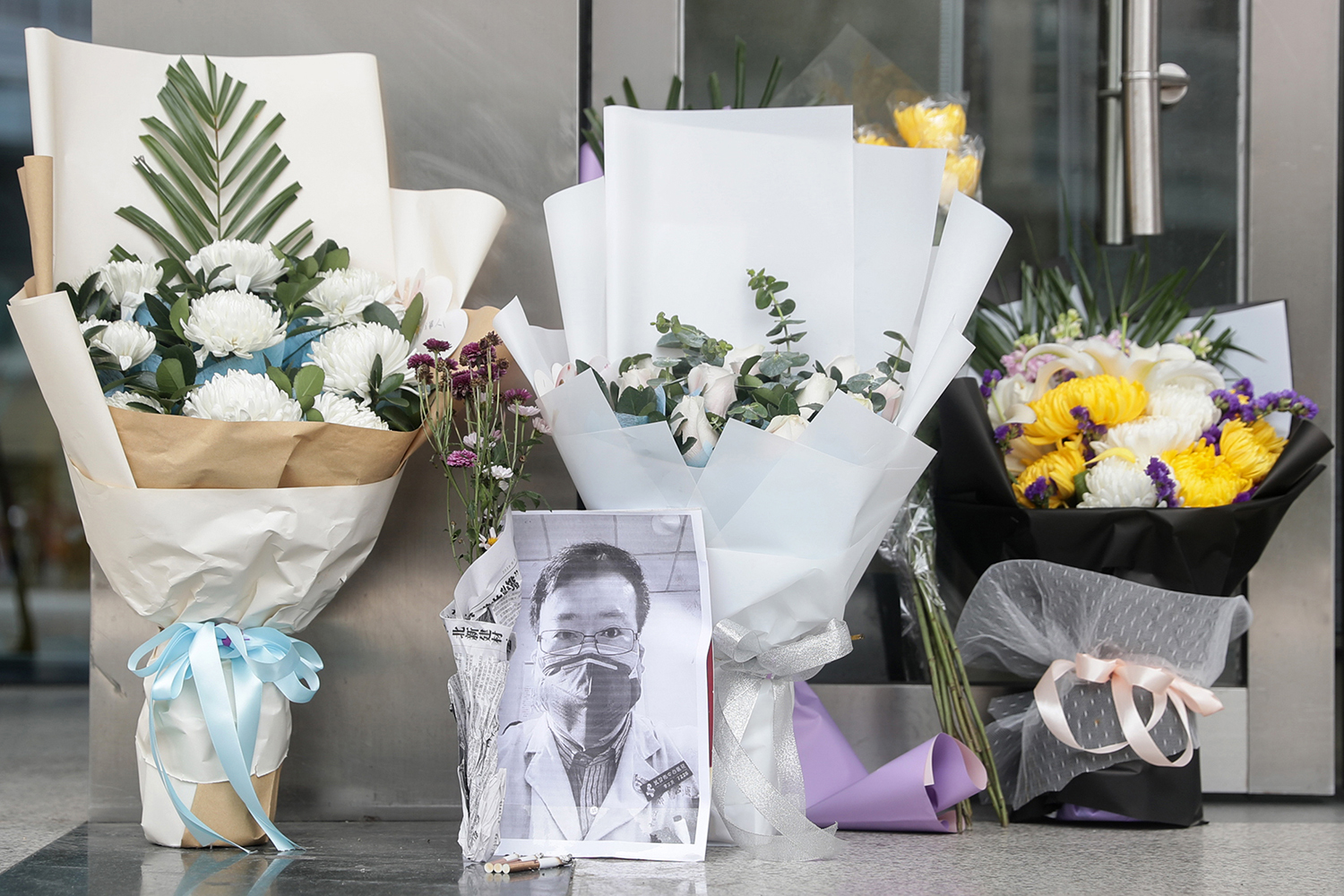 A photo of the late ophthalmologist Li Wenliang rests among bouquets at the Houhu Branch of Wuhan Central Hospital on Feb. 7.