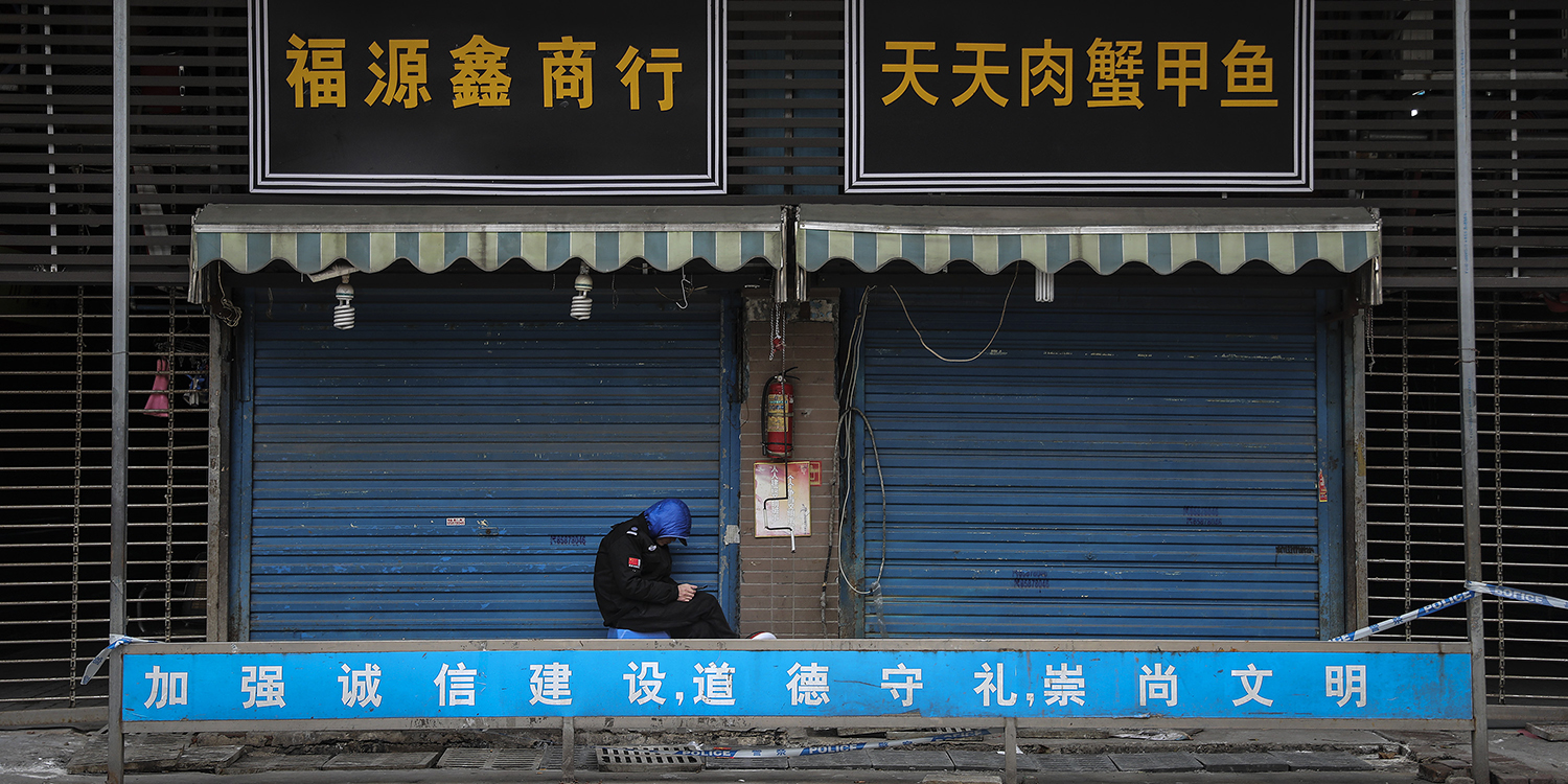 A security guard sits outside the closed Huanan Seafood Wholesale Market, which was linked to cases of coronavirus, in Wuhan, China, on Jan. 17.