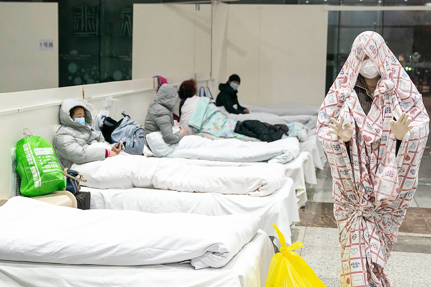 A patient walks between hospital beds shrouded in a sheet, gloves, and a face mask at the exhibition center converted into a hospital in Wuhan on Feb. 5. STR/AFP via Getty Images