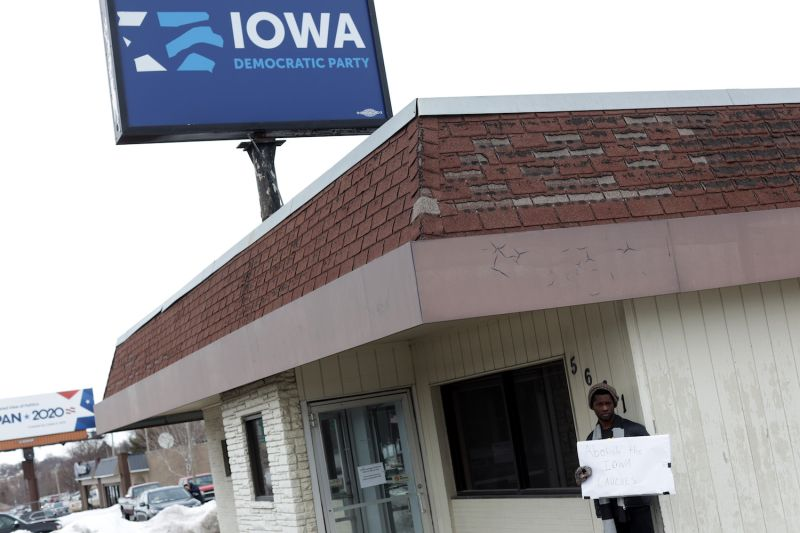 Wallace Mazon holds a sign calling for the abolition of the Iowa caucuses outside the Iowa Democratic Party headquarters in Des Moines on Feb. 4.