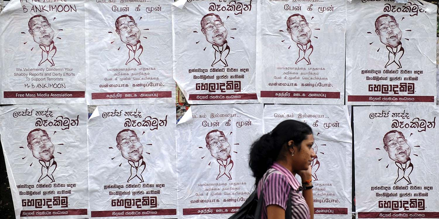 A Sri Lankan pedestrian walks past a poster ridiculing U.N. chief Ban Ki Moon in Colombo on April 25, 2011, ahead of the release of a U.N. report on alleged war crimes.