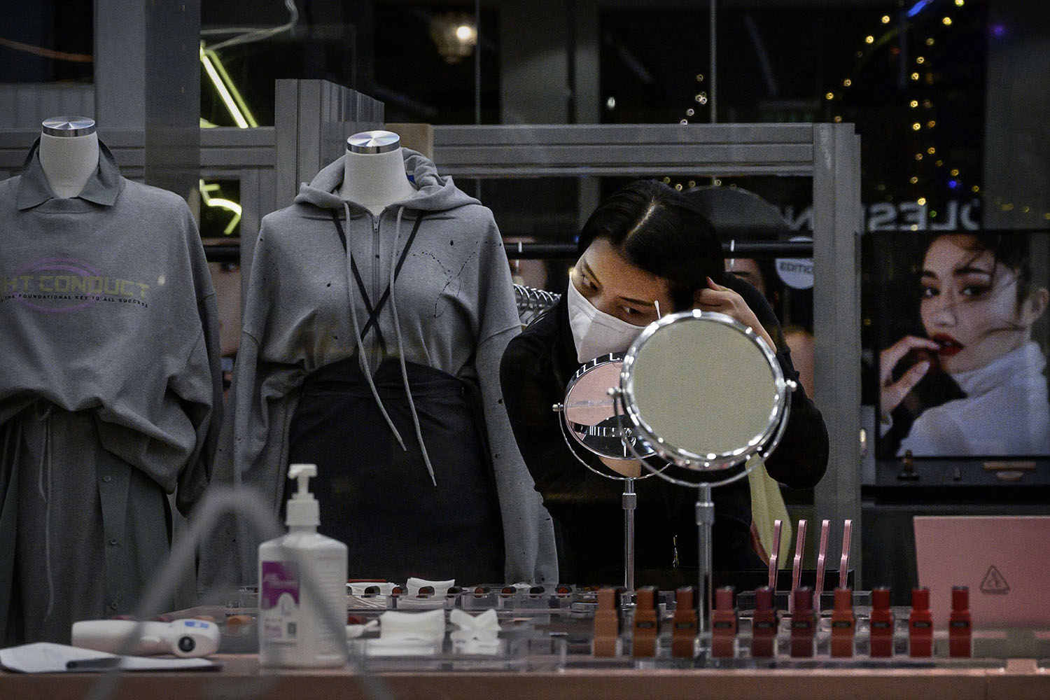 A Chinese woman wears a protective mask as she puts on make-up while waiting for customers at a clothing store in Beijing on Feb. 23.