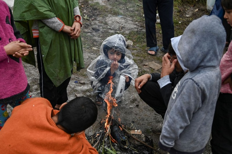 Children warm themselves around a fire.