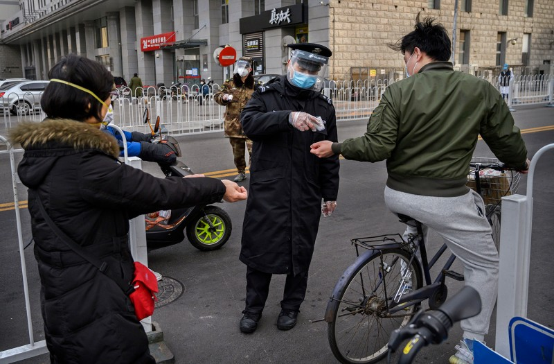 A Chinese security guard checks the temperature of people entering a residential building on Feb. 26 in Beijing.
