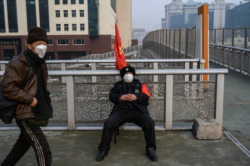 A Chinese guard wears a protective mask as he sleeps in a chair near a footbridge on Feb. 12 in Beijing.