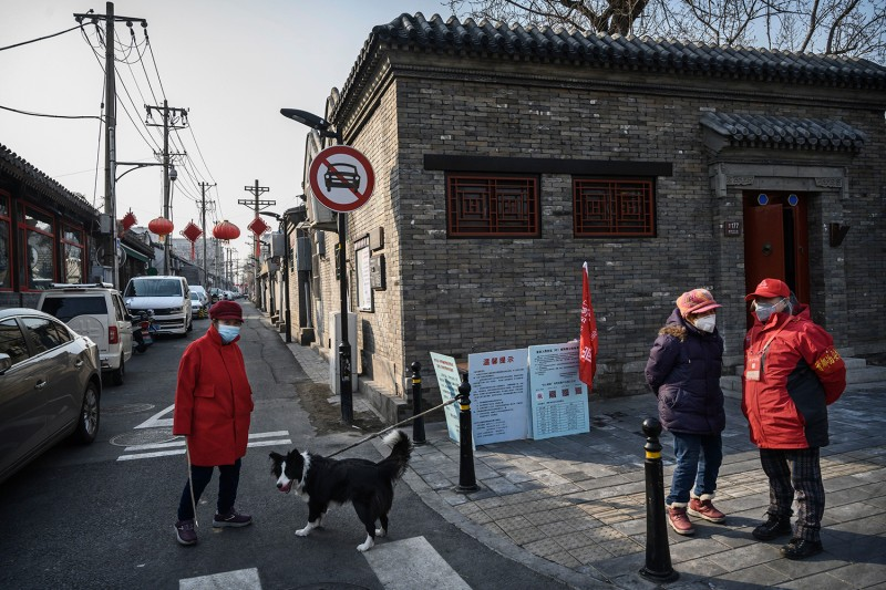 Members of a neighborhood committee wear protective masks as they control the entrance to a narrow street on Feb. 19 in Beijing.