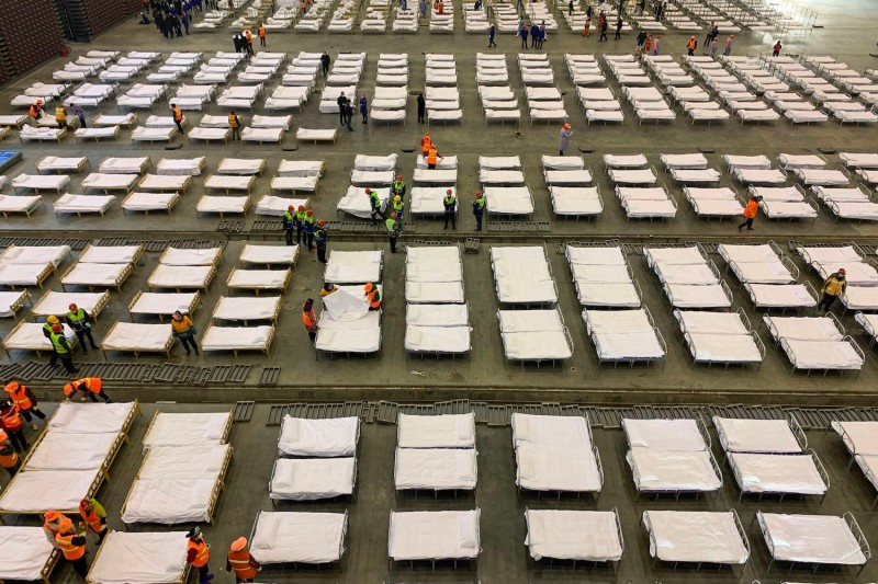 Workers set up beds at an exhibition center that was converted into a hospital in Wuhan, China.