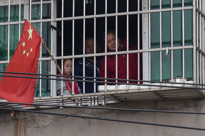 A family looks out the window of their home on the outskirts of Wuhan, China, on Jan. 27 amid the coronavirus outbreak.
