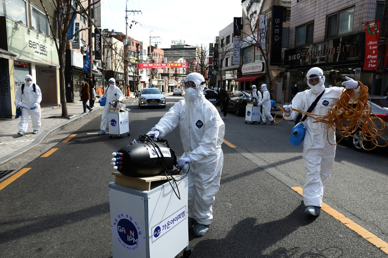 Disinfection professionals spray anti-septic solution against the coronavirus on Feb. 27 in Seoul.