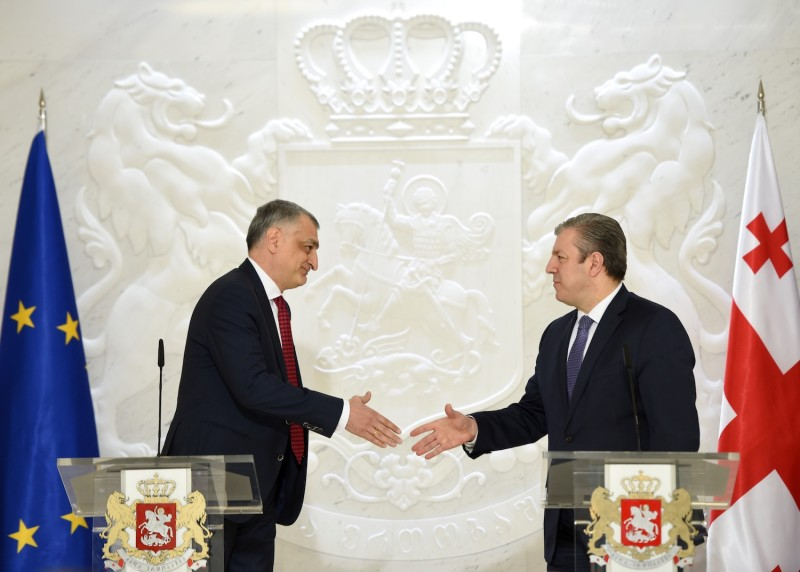Then-Georgian Prime Minister Giorgi Kvirikashvili (right) approaches to shake hands with the then-chairman of Georgia's TBC Holding Mamuka Khazaradze during a press conference.