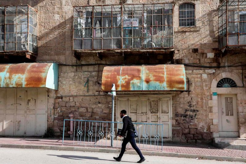 An Israeli settler walks past a Palestinian house with verandas covered in meshing along the Israeli-controlled Shuhada street in the West Bank city of Hebron on Jan. 28.
