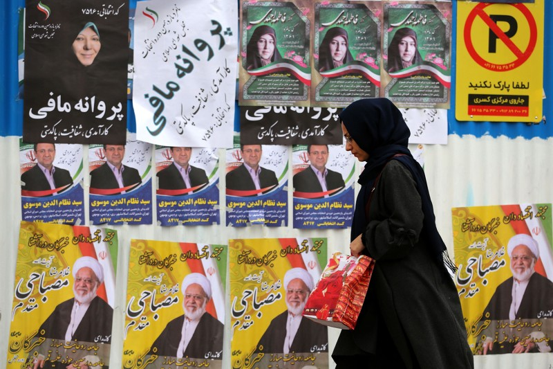 An Iranian woman walks past electoral posters and fliers during the last day of the parliamentary election campaign in Tehran on Feb. 19.