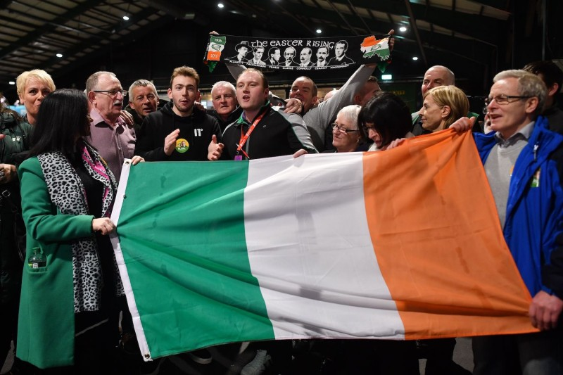 Sinn Fein supporters sing as they hold an Irish flag during the Dublin City count.