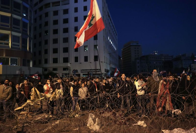 Anti-government demonstrators rally behind barbed wire.