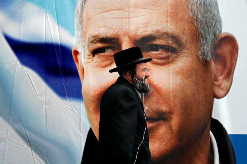 An Ultra-Orthodox Jewish man walks past an electoral billboard bearing a portrait of Israel's Prime Minister Benjamin Netanyahu, in Jerusalem, on April 1, 2019.