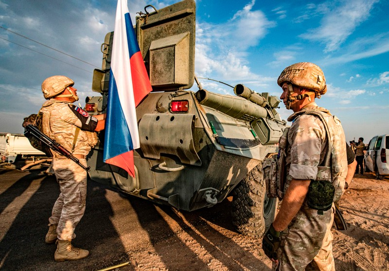 Russian military police stand near an armored personnel carrier in Syria's Hasakeh province on Oct. 24, 2019.