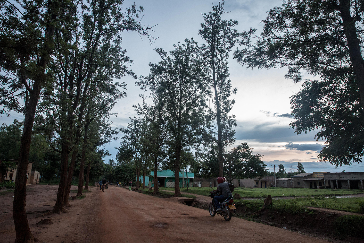 A boda boda driver drives down the main road in Gashora, Rwanda, where hundreds of refugees are now being sheltered after they were evacuated from Libya, on Nov. 28, 2019.