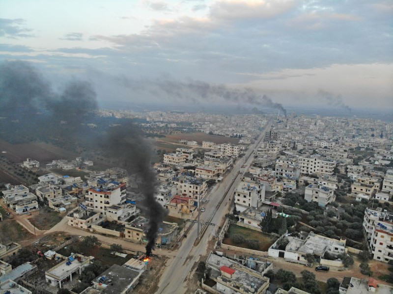 An aerial view taken on Feb. 6, 2020, shows smoke billowing from tires burnt by Syrians in an attempt to hinder air strikes.