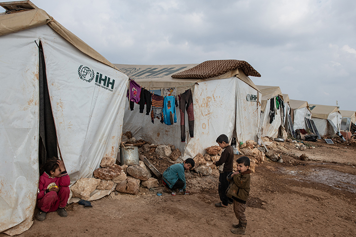 Children play in front of their tent at the Haranabush camp on Feb. 19 in Idlib, Syria.