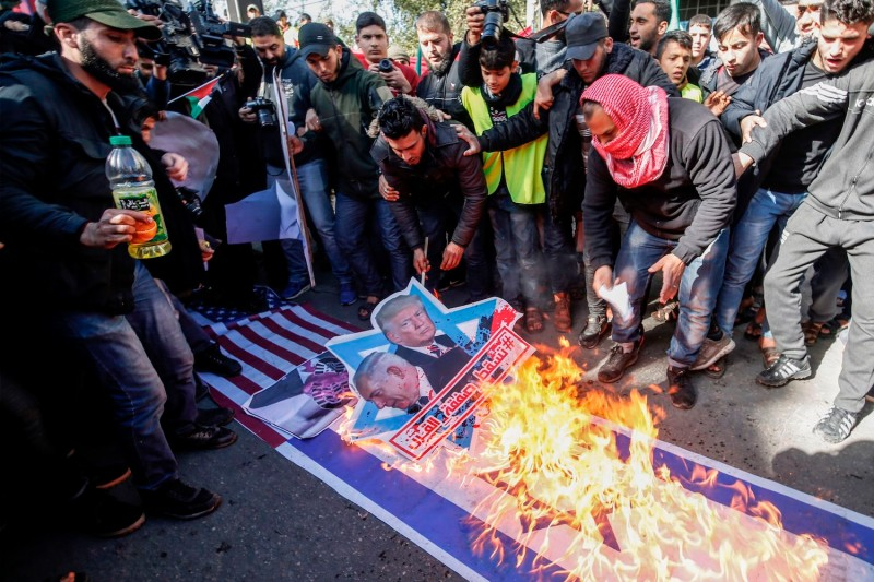 "Palestinian demonstrators burn portraits of U.S. President Donald Trump and Israeli Prime Minister Benjamin Netanyahu with the slogan in Arabic ""Down with the Deal of the Century"" during a protest in Gaza's Jabalia refugee camp on Jan. 31."