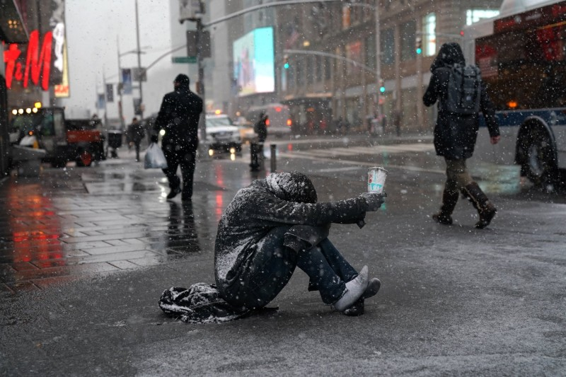 A man begs for money in the snow along 42nd Street in Times Square in New York on March 21, 2018.