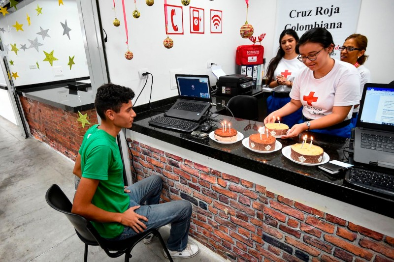 Venezuelan migrant Johan Castillo receives cakes on his birthday from members of the Red Cross in Bucaramanga, Colombia, on Dec. 17, 2019.