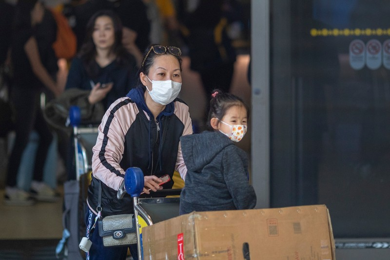 Travelers arrive in Los Angeles, California, wearing medical masks to protect against the Wuhan coronavirus outbreak on Feb. 2.