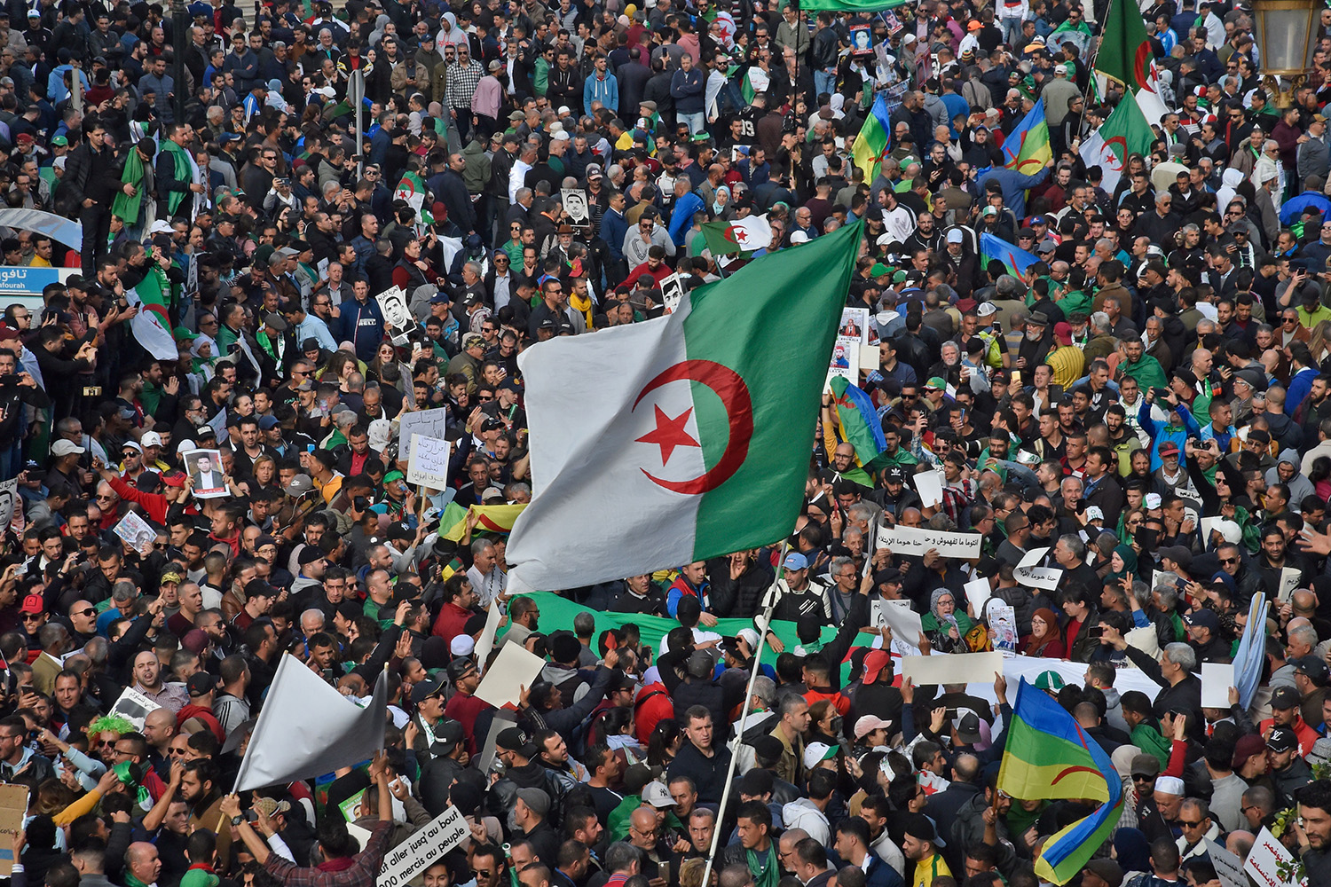 Algerian protesters wave the national flag during their weekly anti-government demonstration in Algiers on Feb. 21. RYAD KRAMDI/AFP via Getty Images