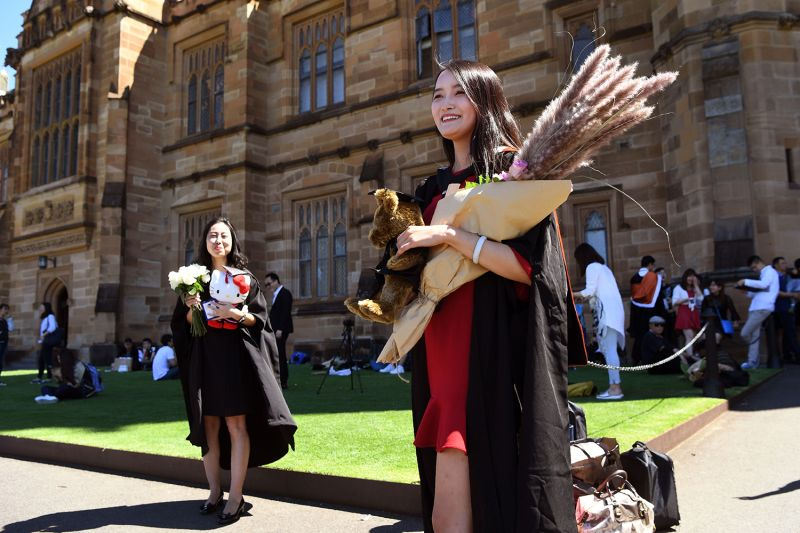 A student from China poses for family photos after graduating from the University of Sydney on Oct. 12, 2017.