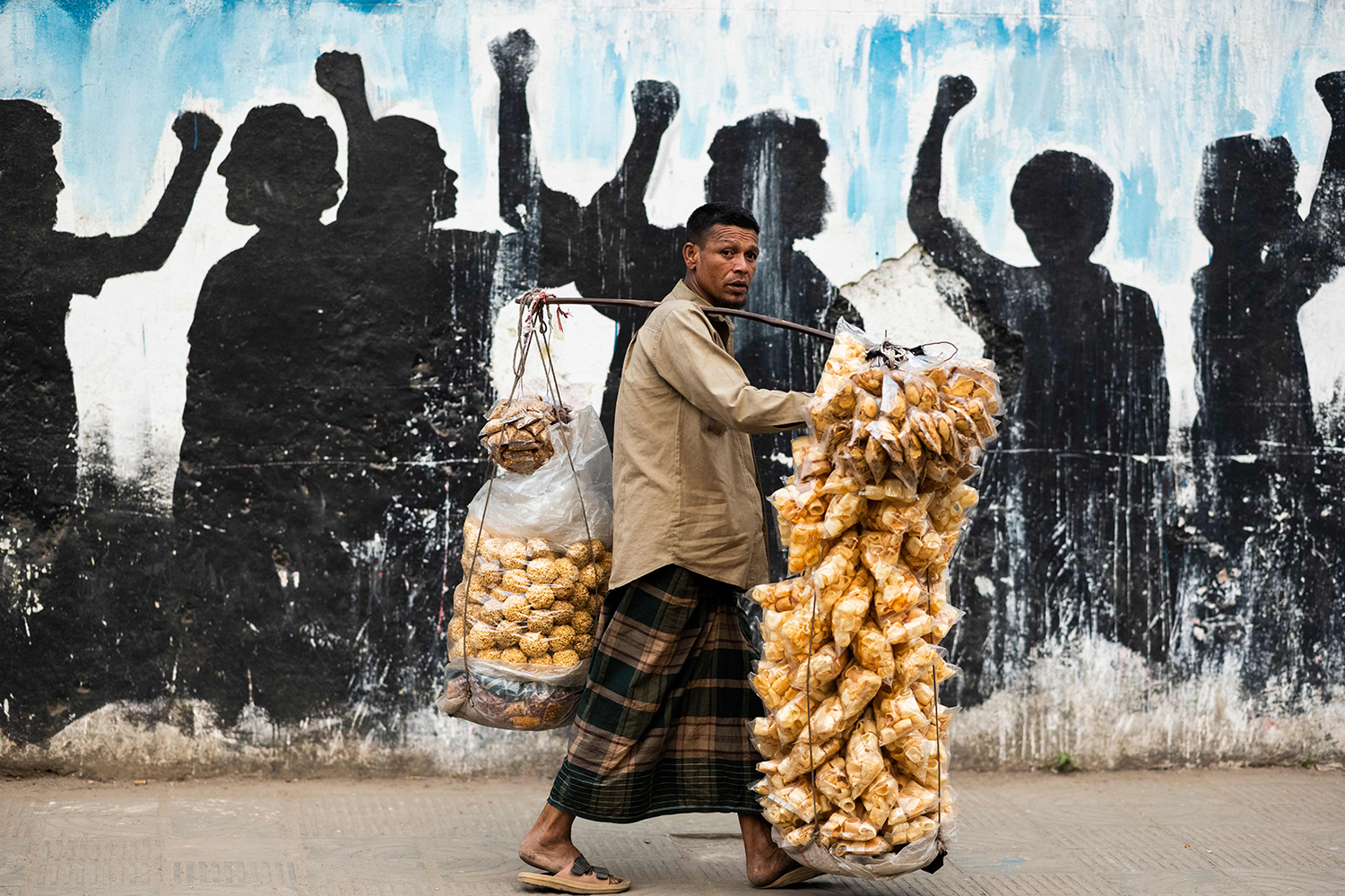 A snack vendor looks for customers along a street in Dhaka, Bangladesh, on March 2. JEWEL SAMAD/AFP via Getty Images