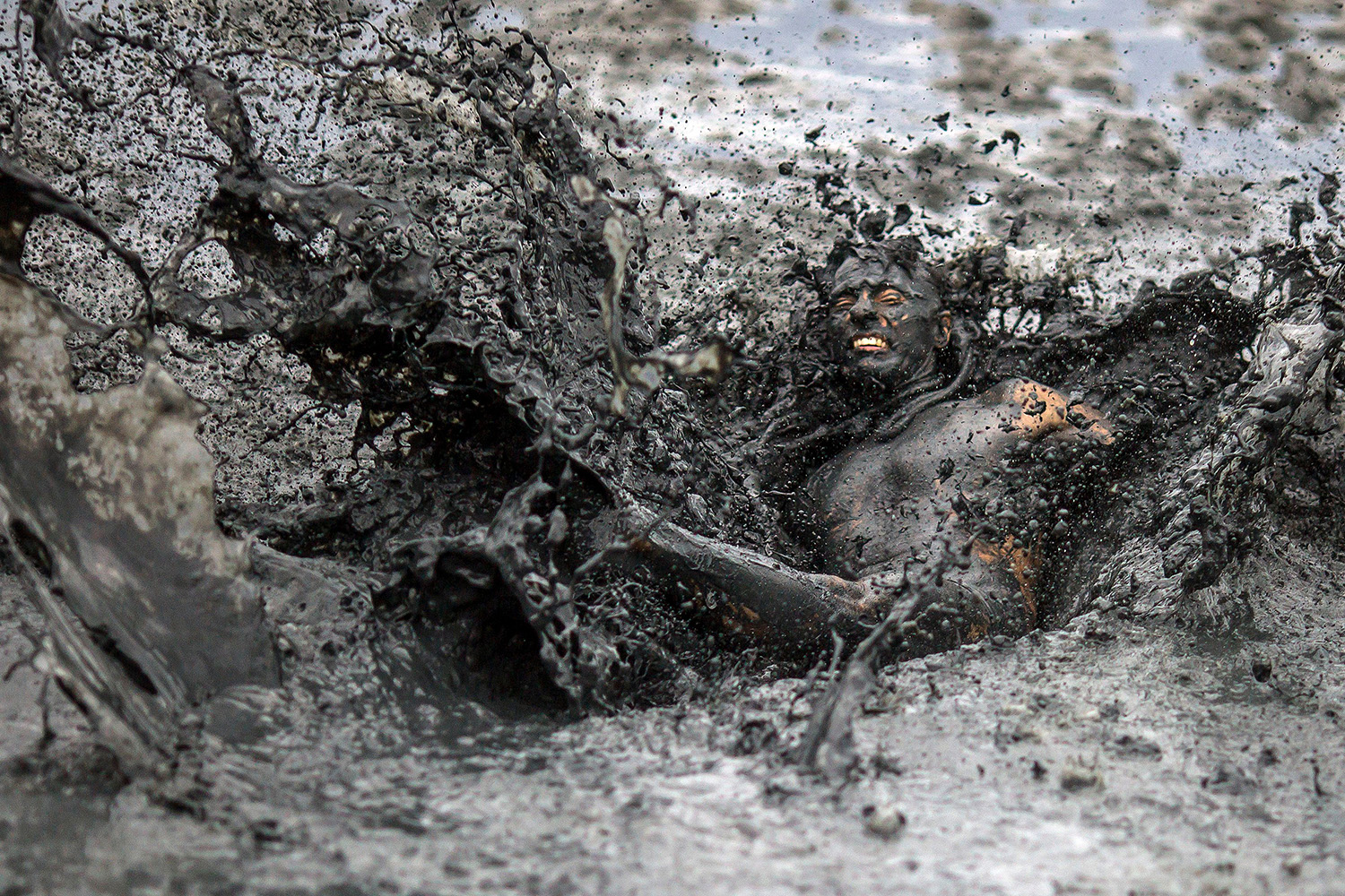 """A reveler jumps in the mud during the Bloco da Lama"""" a mud carnival party, in Rio de Janeiro state, Brazil, on Feb. 22. DANIEL RAMALHO/AFP via Getty Images"""