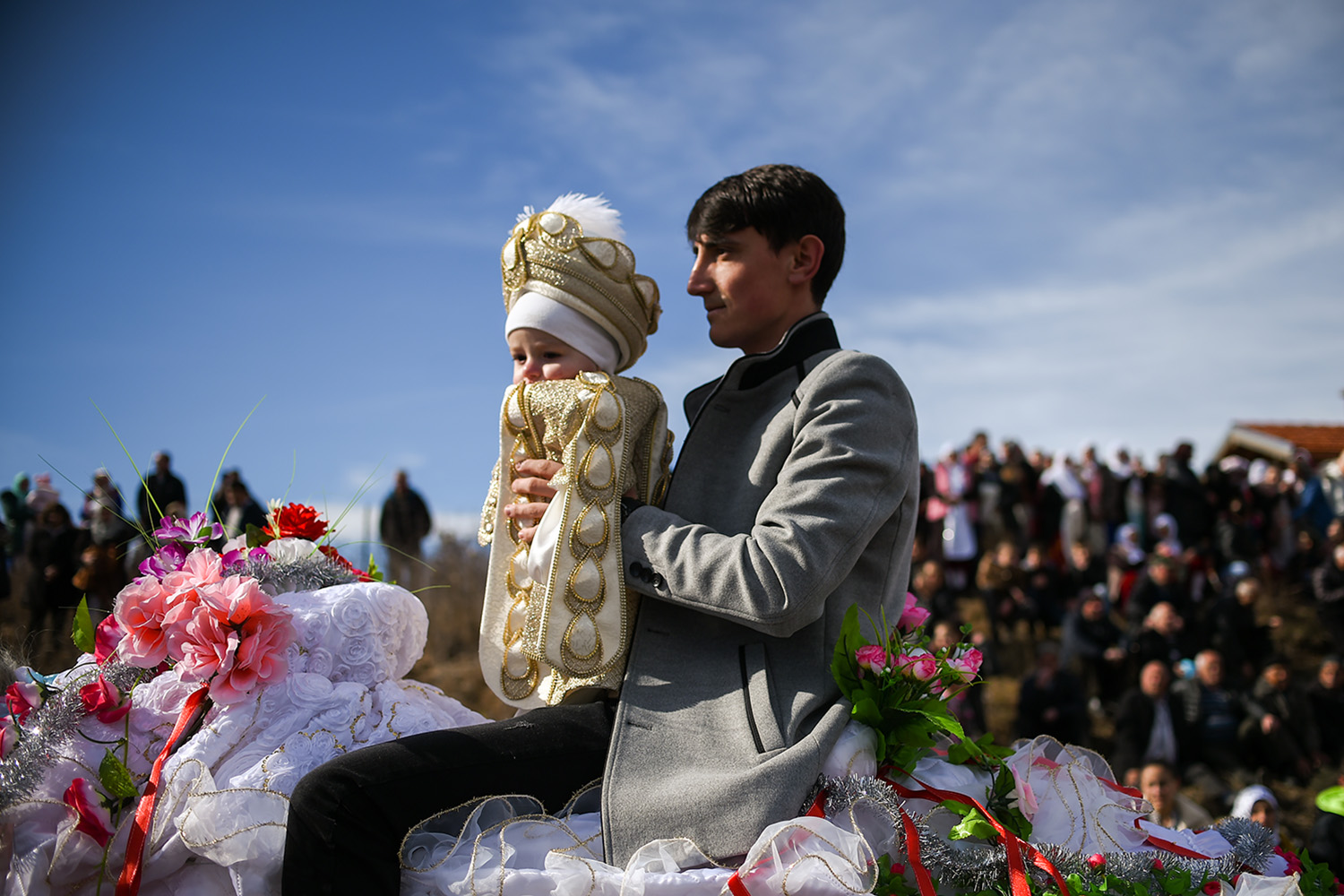 A Bulgarian Muslim man holds his son during a procession, part of a mass circumcision ceremony for young boys, in the village of Ribnovo, Bulgaria, on Feb. 23. NIKOLAY DOYCHINOV/AFP via Getty Images