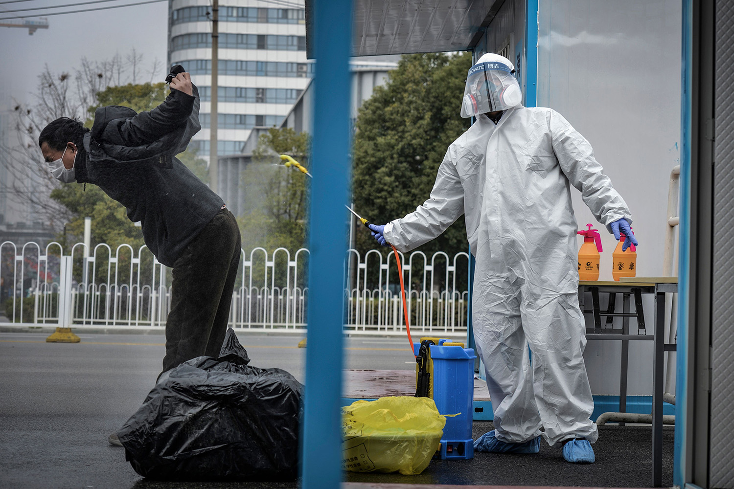 A man who has recovered from the novel coronavirus is  disinfected by medical staff before leaving a hospital in Wuhan, China, on Feb. 22. STR/AFP via Getty Images
