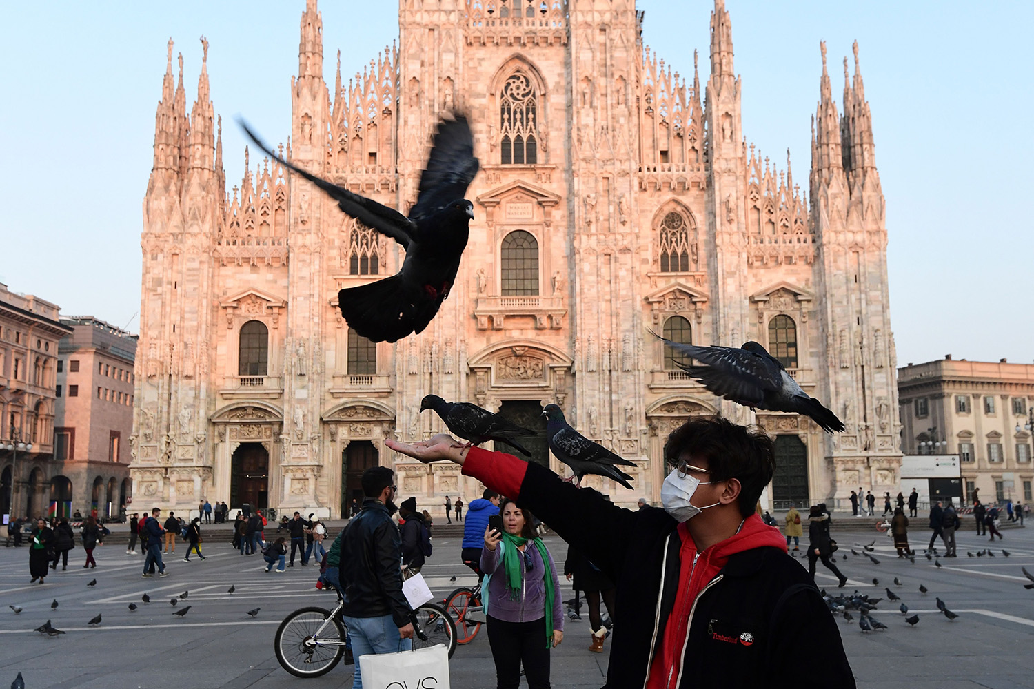 A man wearing a protective mask plays with pigeons in the Piazza del Duomo in central Milan, on Feb. 24, following security measures taken in northern Italy against the novel coronavirus.MIGUEL MEDINA/AFP via Getty Images