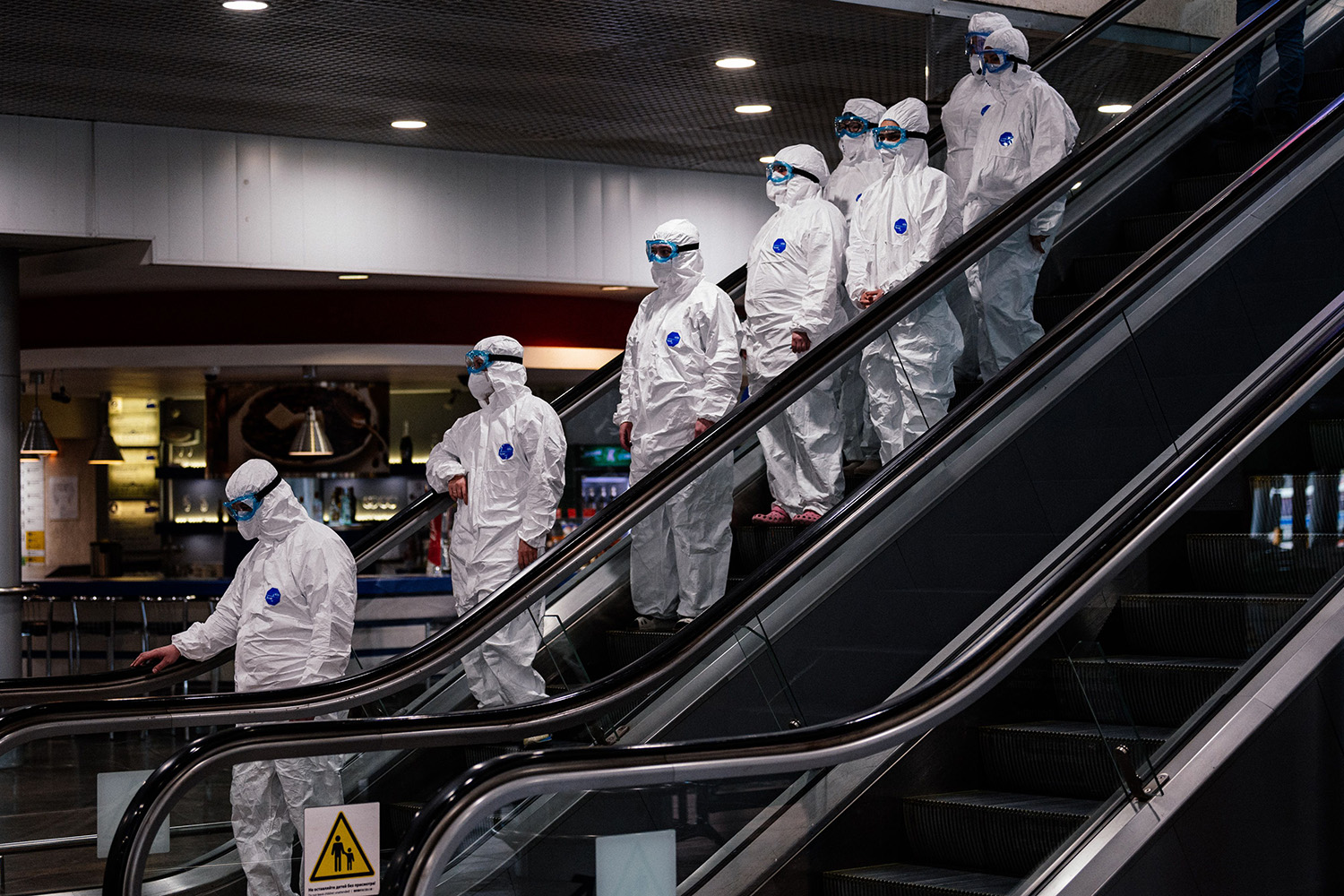 Medical staff wearing protective suits ride down an escalator at Moscow's Sheremetyevo airport March 18. DIMITAR DILKOFF/AFP via Getty Images