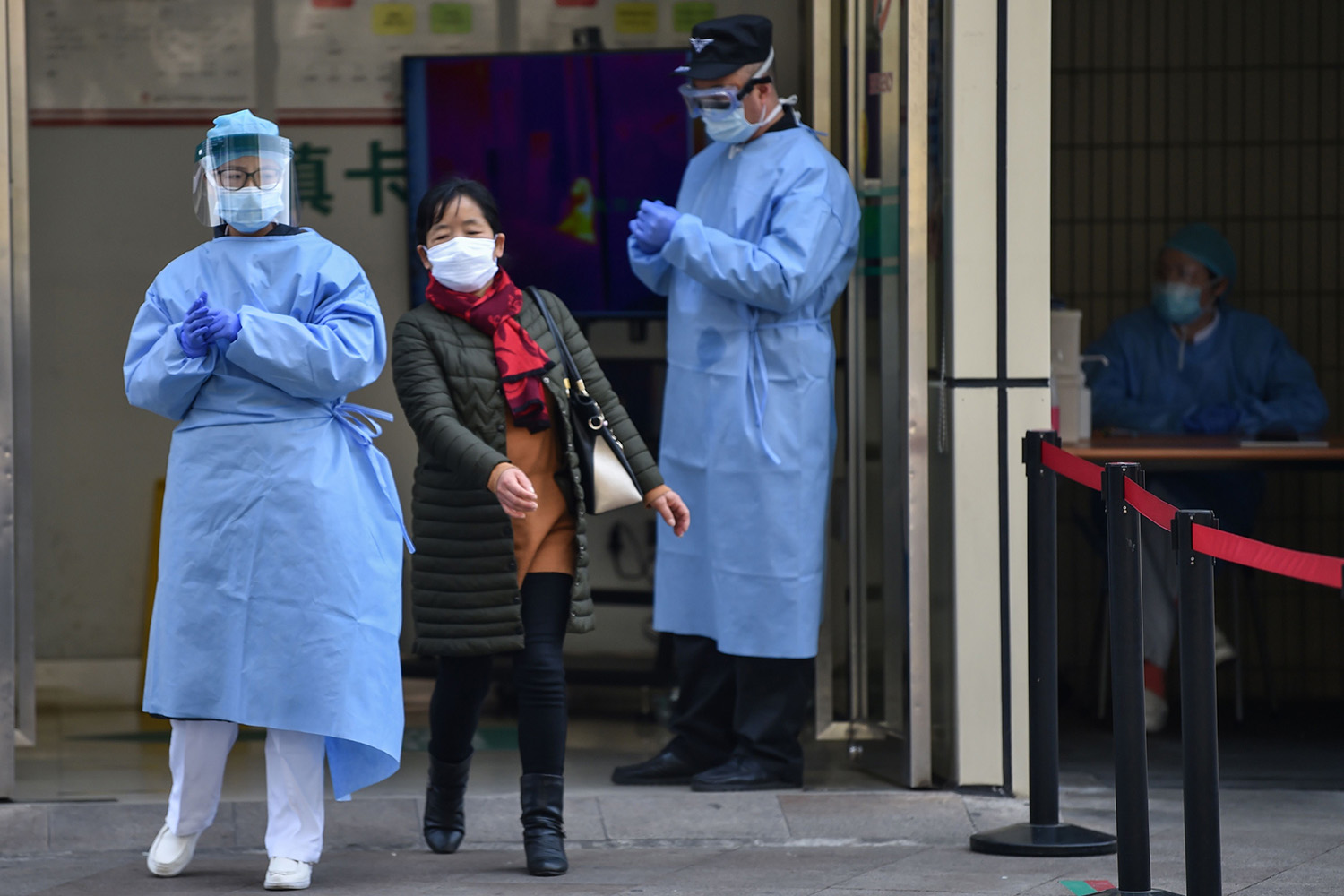 A woman slips past medical staff wearing protective clothing at the entrance of Huashan Hospital in Shanghai on Feb. 27. HECTOR RETAMAL/AFP via Getty Images