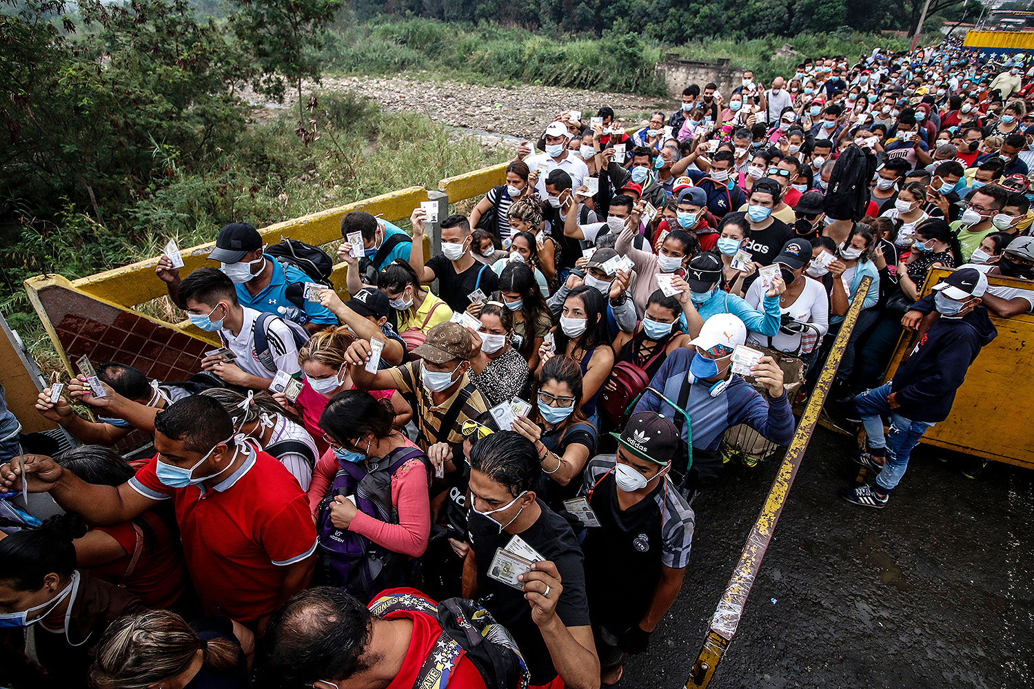 Refugees coming from Venezuela hold up their documents at the border on Simón Bolívar International Bridge in Cúcuta, Colombia, on March 12. SCHNEYDER MENDOZA/AFP via Getty Images