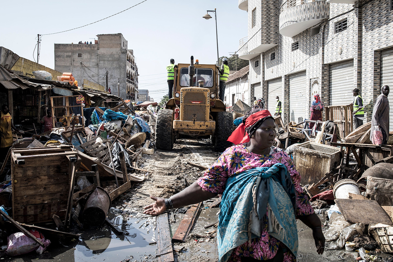A woman protests as a bulldozer clears out stalls in an informal market ahead of disinfecting the Medina neighborhood of Dakar, Senegal, on March 22. JOHN WESSELS/AFP via Getty Images