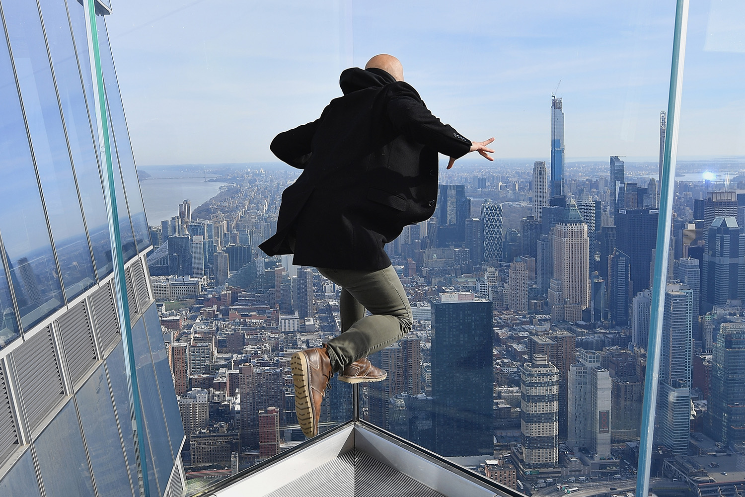 "A man jumps up for a photo at the New York City opening of ""Edge,"" the Western Hemisphere's highest outdoor observation deck, on March 11. ""Edge,"" located on the 100th floor, rises 1,131 feet from the heart of Hudson Yards. ANGELA WEISS/AFP via Getty Images"