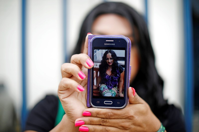 Virginia Flores shows a picture of Camila Díaz Córdova as she waits outside the Attorney General's office in San Salvador, El Salvador, on Feb. 23, 2019.